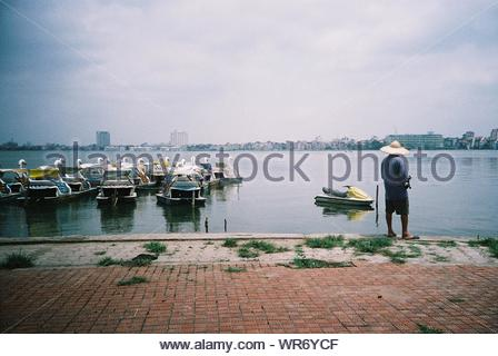 Rear View Of Man Looking At Swan Boats While Standing At Lakeshore Against Cloudy Sky - Stock Photo