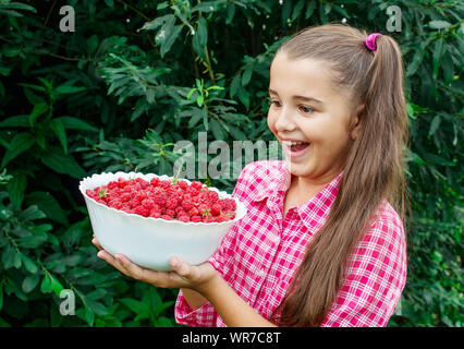beautiful teen girl holding a bowl of raspberries in the garden closeup on summer day - Stock Photo