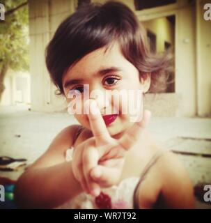 Portrait Of Cute Girl Showing Victory Sign - Stock Photo