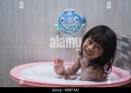 Asian little girl smilling when take a bath with foam - Stock Photo