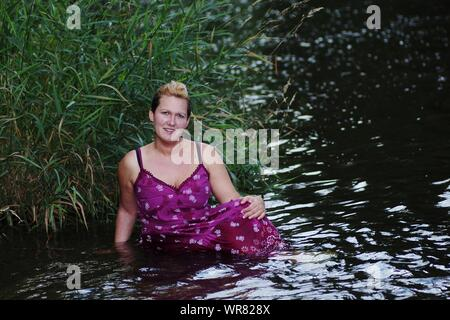 Portrait Of Smiling Woman Standing In Lake - Stock Photo