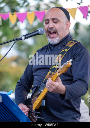 Close up of musician Daniel Jonas of 3yin singing and playing guitar at an annual concert of Jewish Klezmer music in Regent`s Park in London UK. - Stock Photo