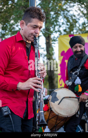 Clarinetist Merlin Shepherd playing concert of Jewish Klezmer music in Regent`s Park London UK. Drummer Jonny Kalsi from the Dhol Foundation at back - Stock Photo