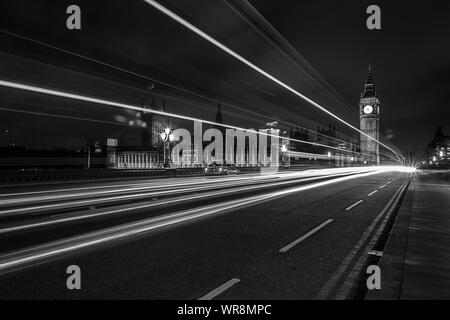 Light Trails On Westminster Bridge Against Illuminated Big Ben At Night - Stock Photo