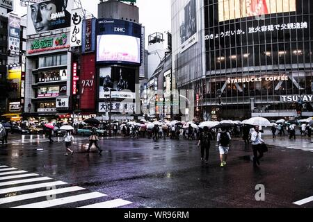 People Carrying Umbrella Walking On City Street Against Buildings During Rainy Day - Stock Photo