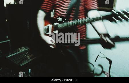 Midsection Of Man Playing Bass Guitar In Music Studio