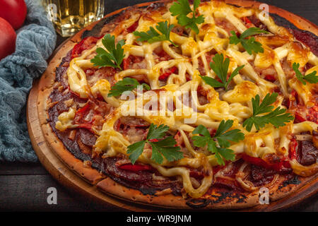 Homemade pizza with meat, sausage, cheese and tomatoes - Stock Photo