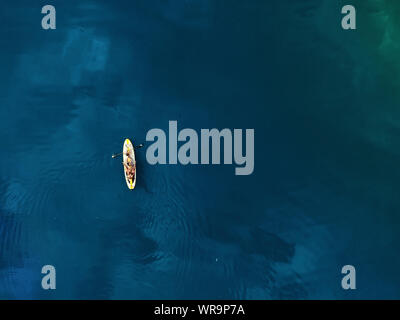 Aerial drone view of family having fun swimming on SUP stand up paddle inflatable surf board. Mother with children enjoy sitting on surfboard at clear - Stock Photo