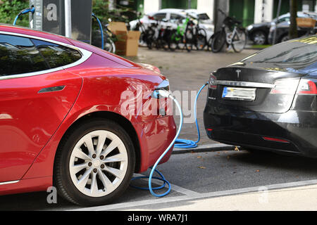 Two TESLA e-cars are being charged at charging stations in Muenchen in the district of Lehel. Electric car e-car is charging, charging plug, charging cable, e-mobility, electrification. Car manufacturer, car, cars, automobiles, manufacturers, car industry, premium brand. | usage worldwide - Stock Photo