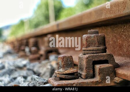 Close-up Of Rusty Old Nuts On Railroad Tracks - Stock Photo