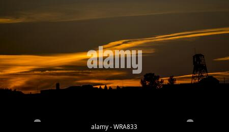 Scenic View Of Dramatic Sky Over Town During Sunset - Stock Photo