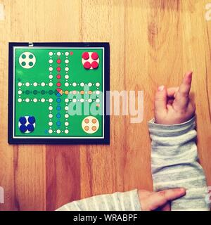 High Angle View Of Child Playing Ludo On Wooden Table - Stock Photo