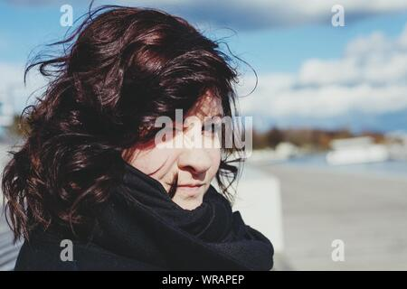 Portrait Of Woman Winking Against Sky - Stock Photo