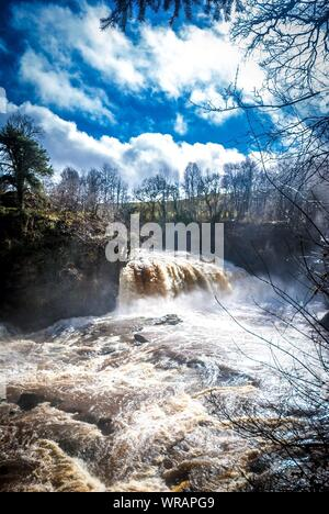 Scenic View Of Waterfall Against Cloudy Sky - Stock Photo