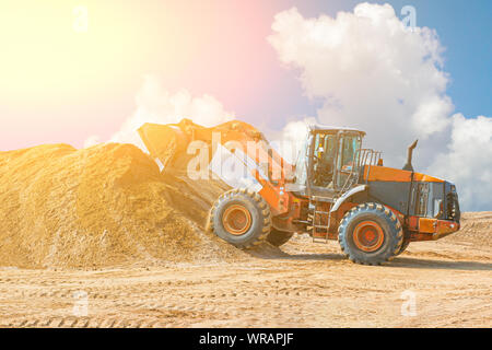 Yellow excavator on a construction site against blue sky. wheel loader at sandpit during earthmoving works. - Stock Photo