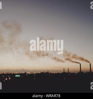 Smoke Emerging From Chimneys Against The Sky At Night - Stock Photo