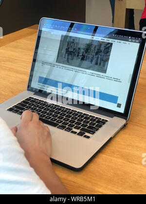 A Chinese netizen browses the introduction of Gait Recognition on the website of AI technology company Watrix on his Apple laptop computer in Beijing, - Stock Photo