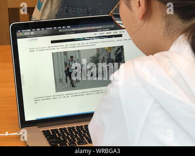 A Chinese netizen browses the introduction of Gait Recognition on the website of AI technology company Watrix on her Apple laptop computer in Beijing, - Stock Photo