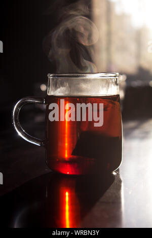 Morning sun falls on vapor rising from a glass cup of tea with teabag inside on wooden table. The glass of tea has a reflection on the polished table. - Stock Photo