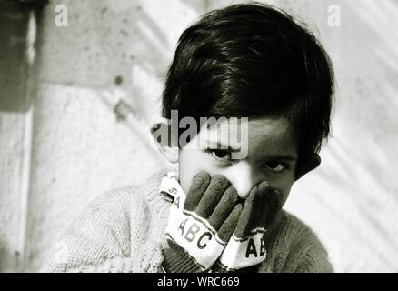 Close-up Of Cute Boy With Hands Covering Mouth - Stock Photo