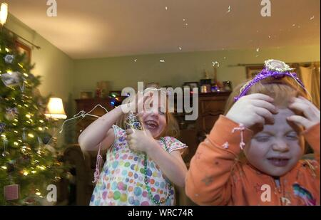 Cheerful Siblings During Christmas At Home - Stock Photo