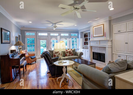 Beautiful living room with fireplace and lots of windows - Stock Photo