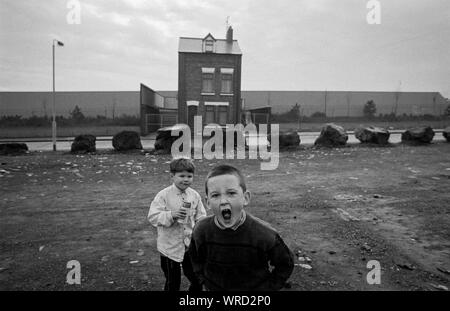 Children play in front of a solitary house, which is surrounded by a 'peace wall', in Roe Street, North Belfast, Northern Ireland, in December 1992. - Stock Photo