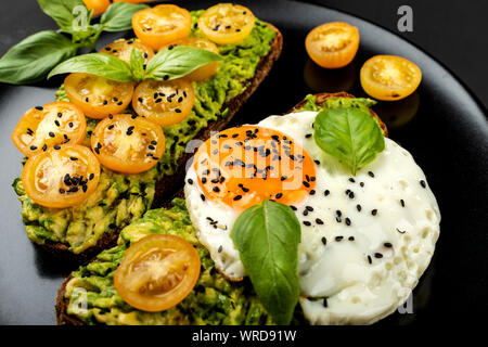 Open sandwiches with avocado guacamole, yellow cherry tomatoes, fried egg and basil on a black plate on the black background. Close-up. - Stock Photo