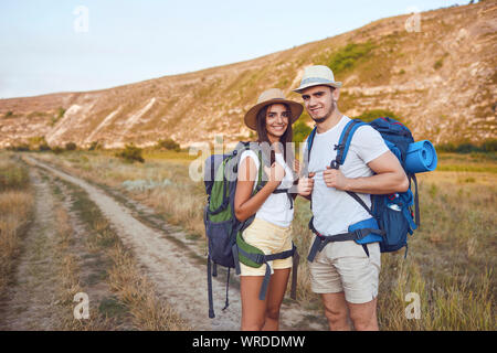 Couple hikers with backpack walking on hike in nature - Stock Photo