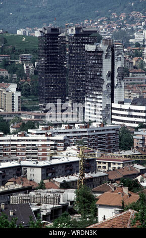 20th May 1993 During the Siege of Sarajevo, the view of the city from Bosnian Serb lines at Vraca Memorial Park on Mount Trebevic. Prominent in the frame are the badly damaged twin Unis towers and the tower of the Executive Council/Assembly Building, peppered with shell holes and mostly gutted by fire. - Stock Photo