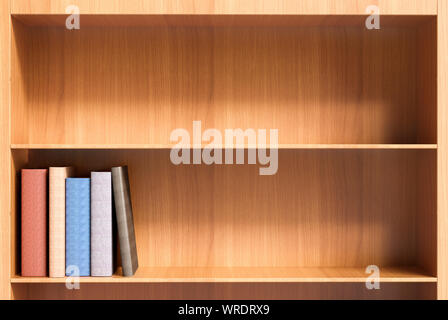 Two shelves (one empty) of a wooden bookcase with a few hardback books with blank spines - Stock Photo