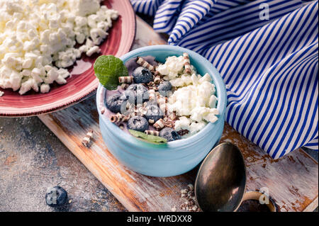 Close-up curd sweet dessert with fresh blueberries in blue deep bowl. Healty breakfast - Stock Photo