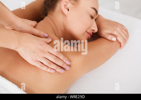 Millennial woman receiving shoulder massage in the spa - Stock Photo