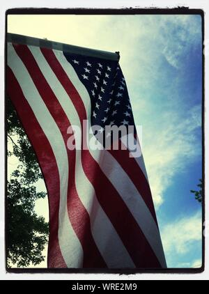 Low Angle View Of American Flag Fluttering Against Sky - Stock Photo
