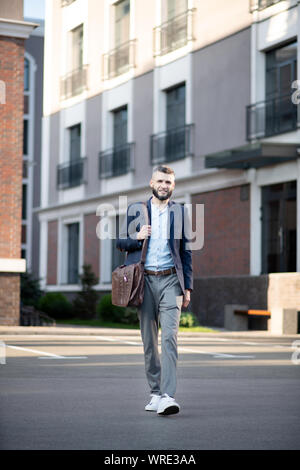 Bearded man leaving house and walking to office - Stock Photo