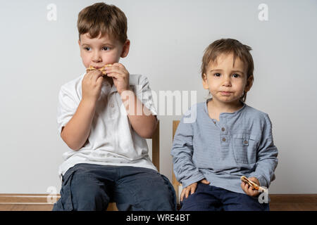 Children sitting at cafeteria table while eating lunch. Smiling kids with sandwiches. Pizza at school. Eating together. - Stock Photo