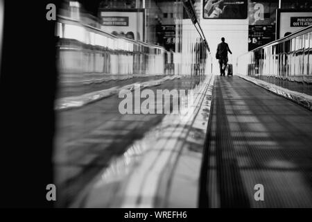 Rear View Of Man On Moving Walkway At Airport
