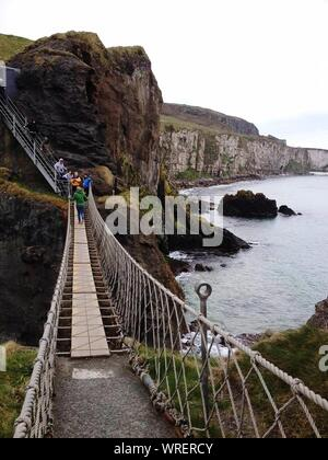 High Angle View Of Tourists On Carrick-a-rede Rope Bridge In Northern Ireland - Stock Photo