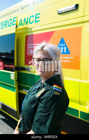 A NHS Ambulance crew member wearing Gay Pride epaulettes standing in front of an ambulance at the Cornwall Gay Pride parade in Newquay Town centre. - Stock Photo