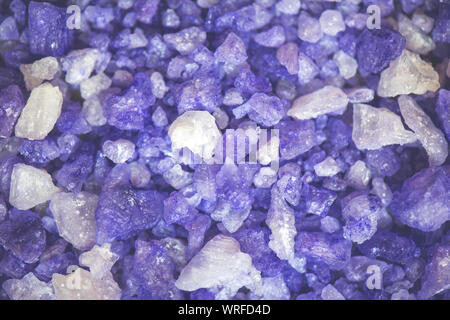 Violet crystals of natural sea salt with lavender close-up background. - Stock Photo