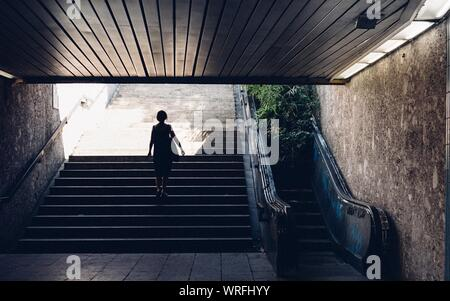 Rear View Of Woman On Steps In Tunnel - Stock Photo