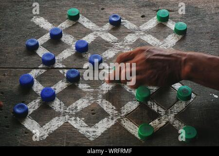 Man Playing Game Of Checkers On Wooden Board Using Bottle Caps - Stock Photo