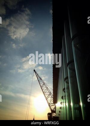 Low Angle View Of Silhouette Crane And Columns Against Sky During Sunset - Stock Photo