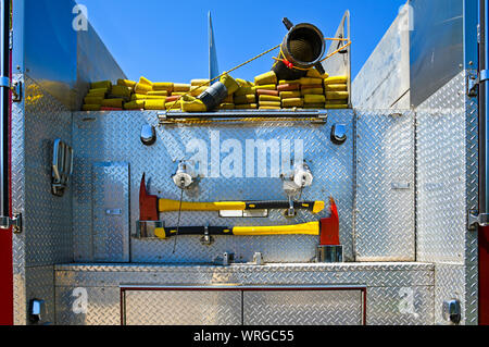 Close-up Image of the Rear of a Fire Truck with Fire Hose and Emergency Axes