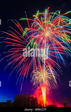 4th of July fireworks over a mountain meadow at dusk, Stowe, Vermont, USA. - Stock Photo