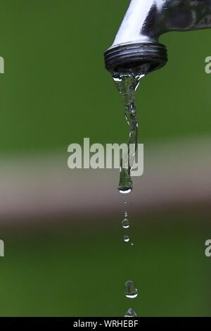 Tropfender Wasserhahn mit stehenden Tropfen in der Luft | Makroaufnahme * Dripping faucet with standing drops in the air | In slow motion - Stock Photo