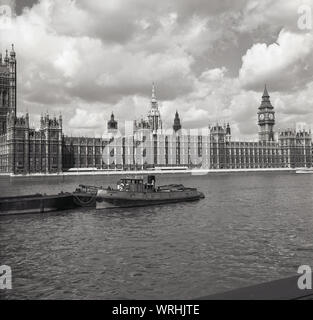 1950s, historical, a view across the river Thames, showing a barge on a mooring and the Palace of Westminster, where the two of Houses of Parliament function, the seat of the UK Government, Westminster, London, England, UK. - Stock Photo
