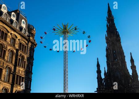 The Star Flyer ride next to the Scott Monument, part of Edinburgh's Christmas attractions in Princes Street Gardens, Edinburgh, Scotland - Stock Photo