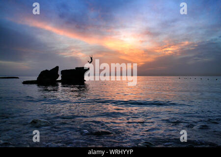 Woman Jumping Off Cliff In Sea - Stock Photo