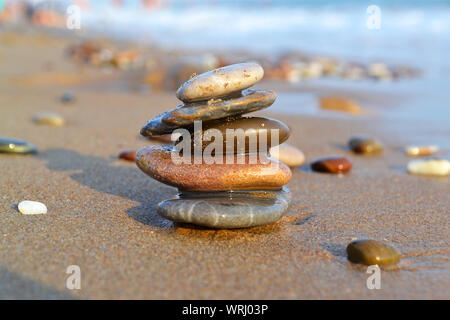 Close-up of zen standing stones 'tower' made of different colours pebble, selective focus on the Summer beach background - Stock Photo